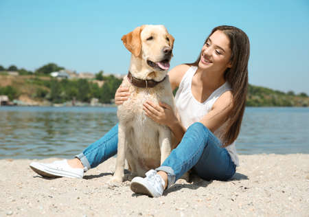Young woman resting with yellow retriever near river Stock Photo