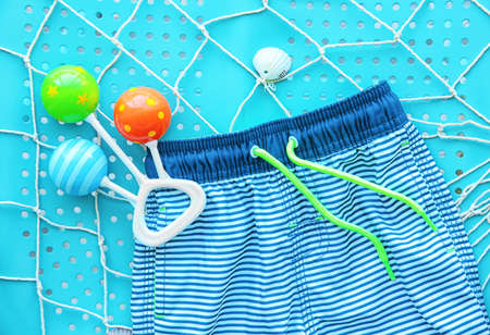 Baby swimming trunks and rattle on blue background, closeup