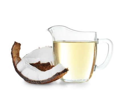 Coco maduro y jarra con aceite aislado en blanco Foto de archivo