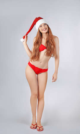 Young sexy lady in Christmas hat and red bikini on light background