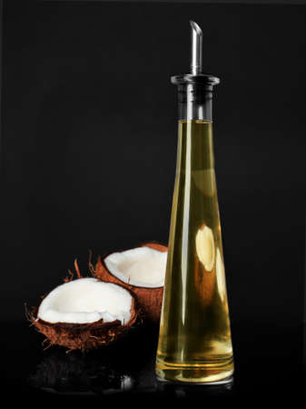 Ripe coconut and bottle with oil on black background