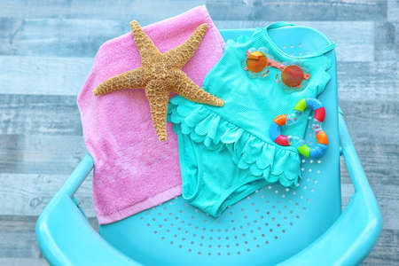 Composition with baby swimsuit and summer accessories on blue chair Stock Photo