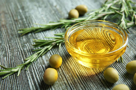 Bowl with cooking oil and rosemary on wooden table Stock Photo