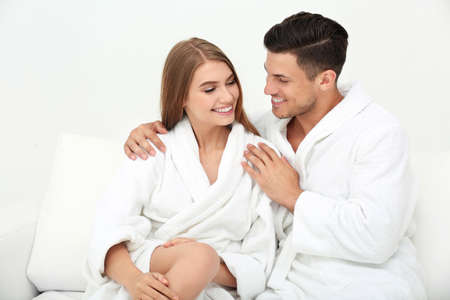 Young loving couple in bathrobes relaxing on sofa Stock fotó