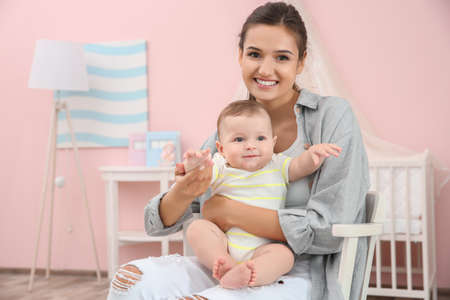 Mother and cute baby sitting on chair after bathing at home Stock Photo