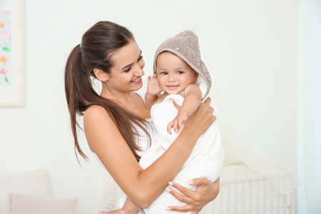 Mother holding cute baby in towel after bathing at home