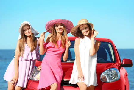 Beautiful young women near car at sea resort