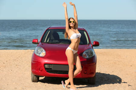 Beautiful young woman near car at sea resort