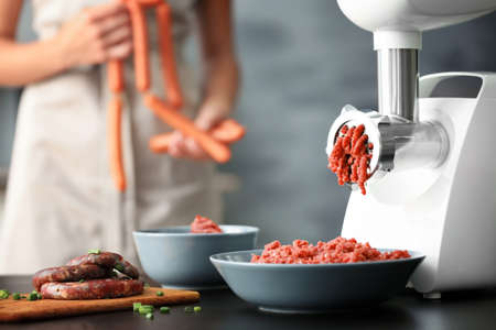 Meat grinder with fresh forcemeat and woman holding sausages in kitchen