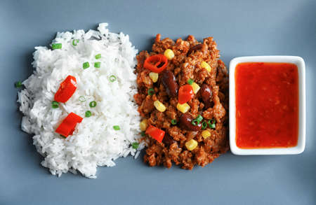 Chili con carne with rice and sauce on grey background