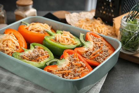 Quinoa stuffed peppers with cheese in baking dish on kitchen table Stock Photo