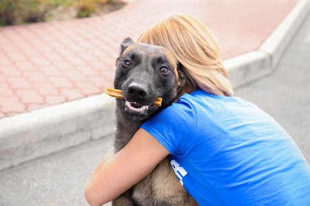 Mujer voluntaria con perro sin hogar al aire libre. Concepto de voluntariado y refugios de animales.