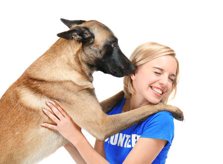 Perro lamiendo a joven voluntario, aislado en blanco. Concepto de voluntariado y refugios de animales.