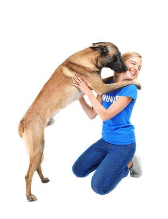 Perro lamiendo a joven voluntario, aislado en blanco. Concepto de voluntariado y refugios de animales. Foto de archivo