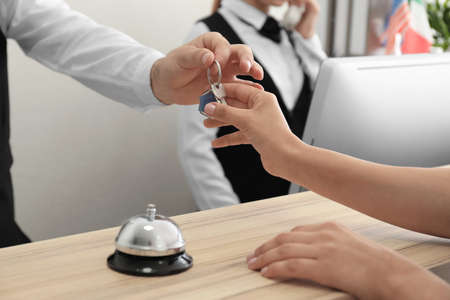Male receptionist handing room key to woman in hotel