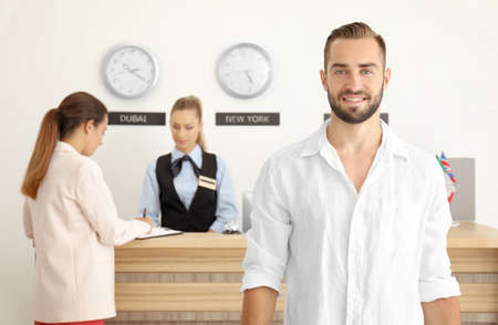 Young man near reception counter in hotel