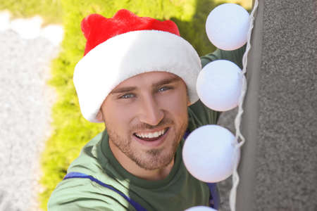 Man in Santa hat decorating facade of house with garland for Christmas