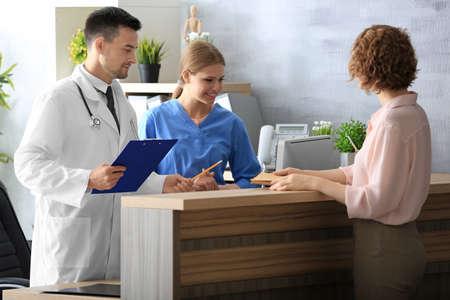 Réceptionniste et médecin avec client à l'hôpital