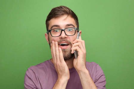 Young man talking by mobile phone against color background