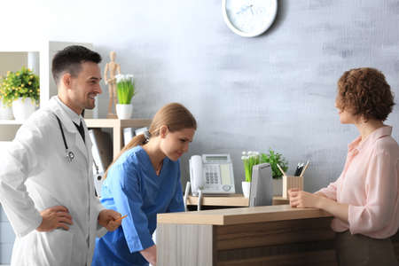 Recepcjonistka i lekarz z klientem w szpitalu