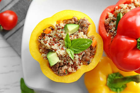 Quinoa stuffed peppers on white plate in kitchen
