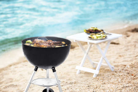 Barbecue grill with tasty steaks and vegetables on beach