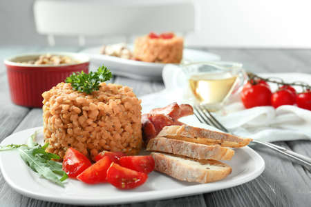 Plate with tasty lentils and sausages on table