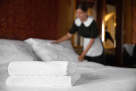 Clean white towels on bed in hotel room and blurred chambermaid on background