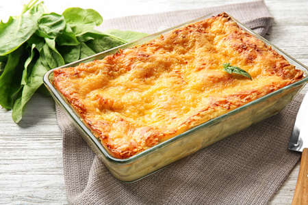 Baking tray with spinach lasagna on table