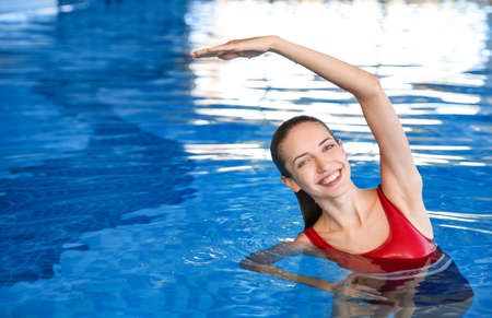 Beautiful young woman exercising in swimming pool Stock Photo