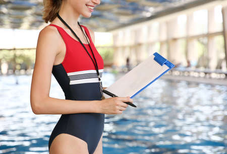 Beautiful young coach with clipboard and pen near swimming pool Stock Photo