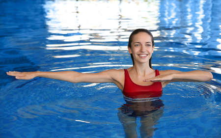 Beautiful young woman exercising in swimming pool 스톡 콘텐츠