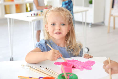Little girl at painting lesson in classroom