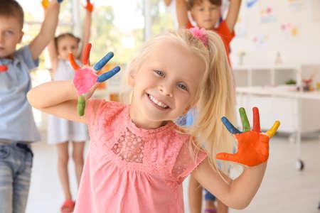 Kleines Mädchen mit den Händen in der Farbe an der Kunststunde