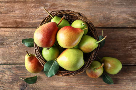 Wicker basket and delicious ripe pears on table