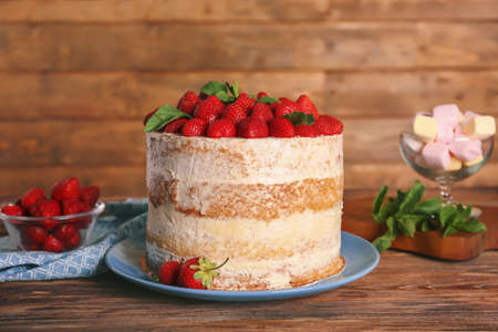 Delicious cake decorated with strawberries on wooden background