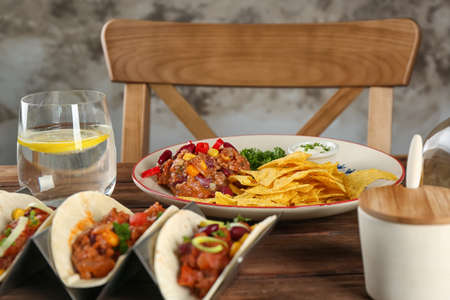 Plate of chili con carne with nachos and tacos on table Stock Photo
