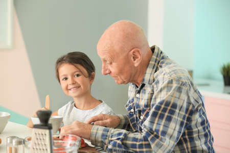 Senior man cooking together with his granddaughter on kitchen