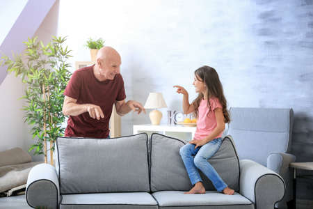 Senior man with his granddaughter at home