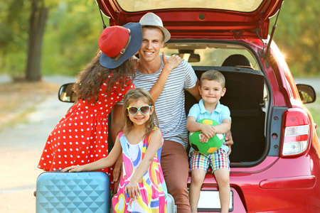 Happy family next to car in countryside Banco de Imagens