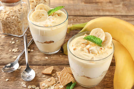 Glasses with delicious banana pudding on table