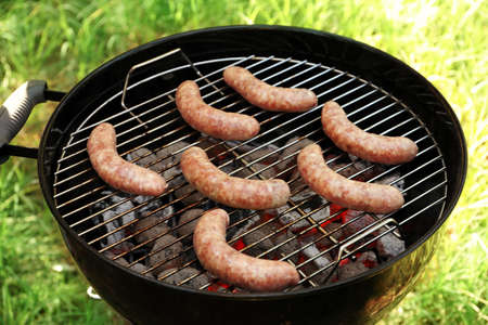 Raw sausages on barbecue grill outdoors Stock Photo