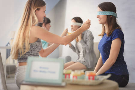 Women taking part in game at baby shower party