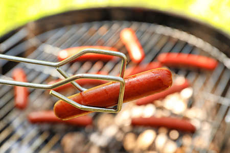 Tongs holding sausage near barbecue grill Standard-Bild