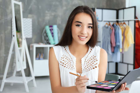Young female blogger with cosmetics at home