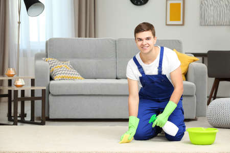Man cleaning carpet in living room