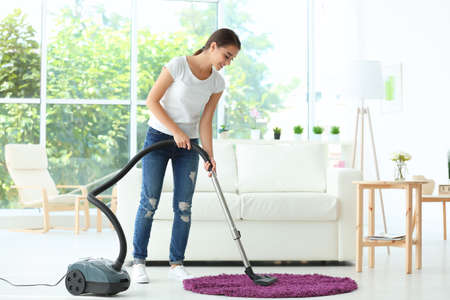 Woman cleaning small rug with vacuum in living room