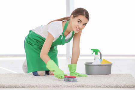 Woman cleaning carpet with brush indoors