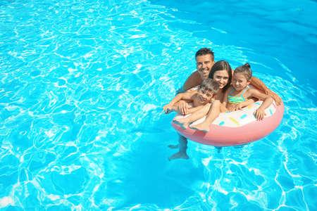 Glückliche Familie mit aufblasbarem Ring, der im Schwimmbad entspannt Standard-Bild