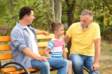 Cute boy with dad and grandfather sitting on bench in park Standard-Bild